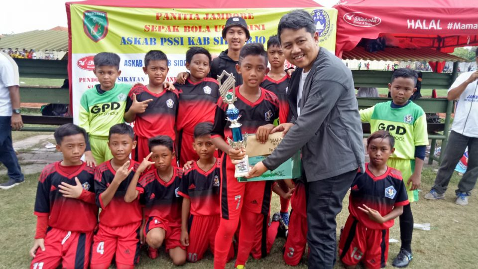 Achmad Amir Aslichin memberikan piala ke tim juara 1 U-10 dalam turnamen sepak bola usia dini di Stadion Jenggolo, Sidoarjo